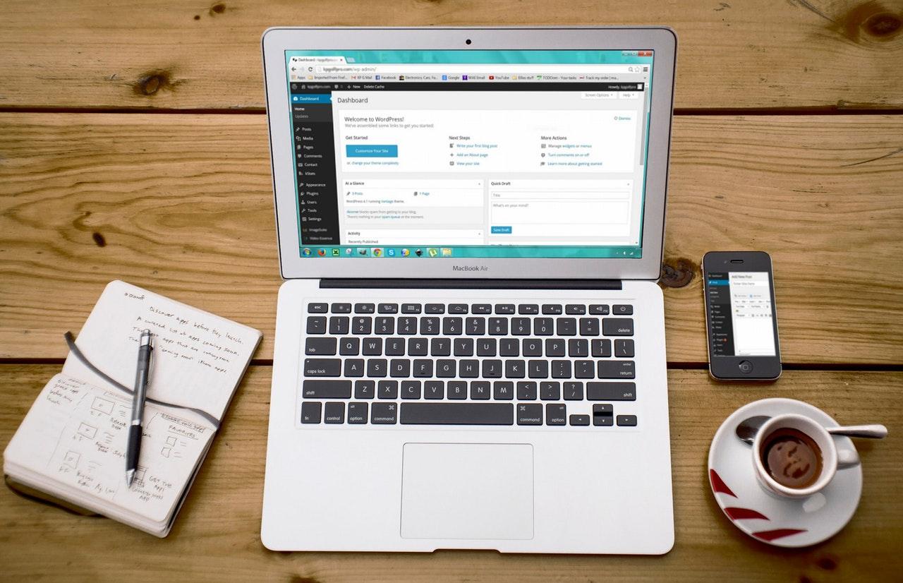 En dator, block och kaffekopp